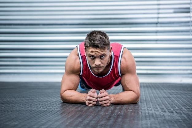 Retrato de homem musculoso em posição de prancha