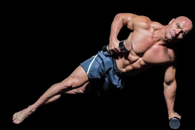 Retrato de homem musculoso exercitando com halteres na pose de prancha lateral