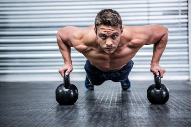 Retrato de homem musculoso fazendo flexões com kettlebells