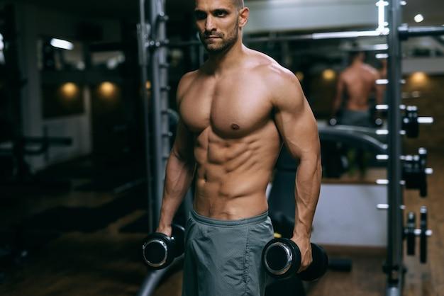 Retrato de homem musculoso sem camisa em pé e segurando halteres nas mãos