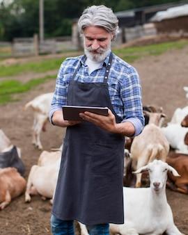 Retrato de homem na fazenda olhando no tablet