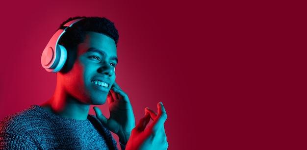 Retrato de homem na parede vermelha do estúdio com luz de néon multicolorida