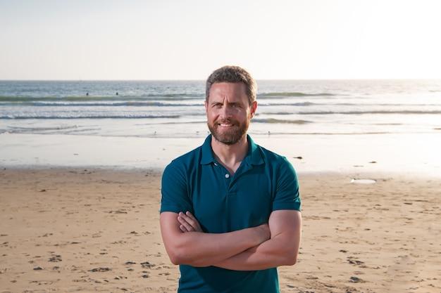 Retrato de homem na praia. jovem bonito vestido casual contra o fundo da praia.