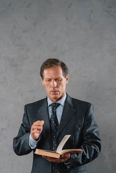 Retrato, de, homem negócios maduro, livro leitura, ficar, contra, cinzento, textured, fundo