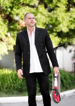Retrato, de, homem negócios, segurando scooter