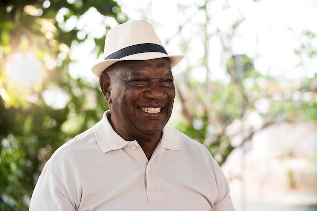 Retrato de homem negro brasileiro sênior com chapéu branco, olhando para um ponto no pôr do sol e sorrindo. forma horizontal, copie o espaço.