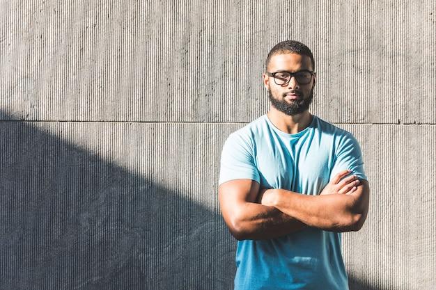 Retrato de homem negro com muro de concreto