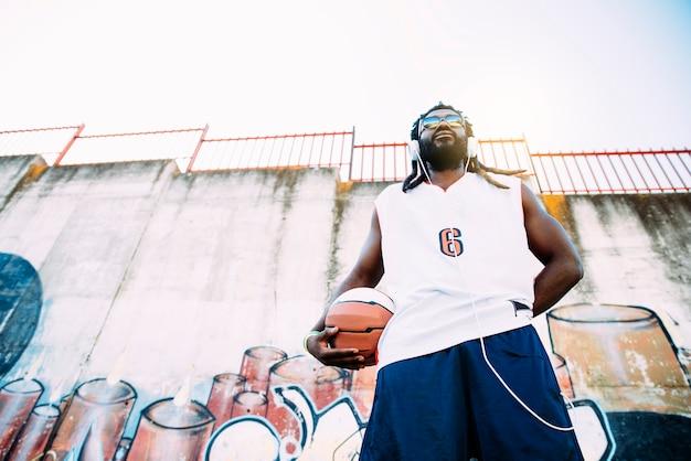Retrato de homem negro com roupas esportivas casuais e bola de basquete.