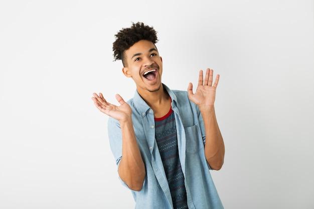 Retrato de homem negro jovem hippie posando no fundo da parede do estúdio branco isolado, roupa elegante, penteado afro engraçado, sorrindo, feliz, expressão do rosto surpreso, chocado, engraçado