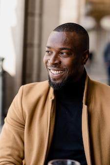 Retrato de homem negro sorrindo, olhando para longe.