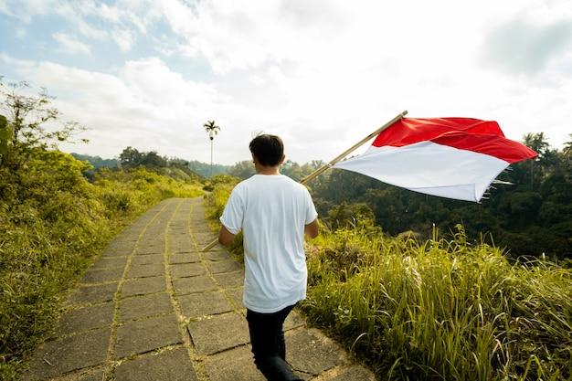 Retrato de homem no topo da colina pela manhã, levantando a bandeira da indonésia, comemorando