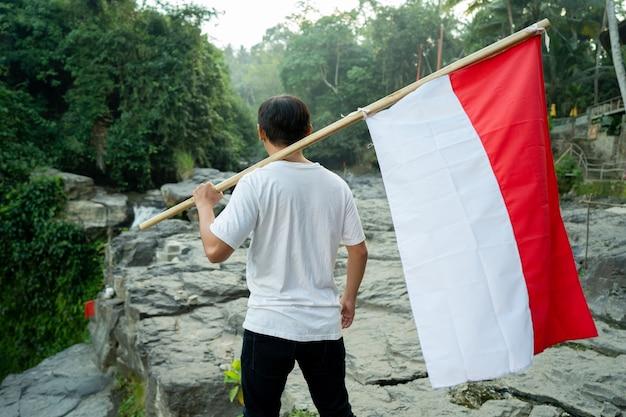 Retrato de homem no topo da colina pela manhã, levantando a bandeira da indonésia