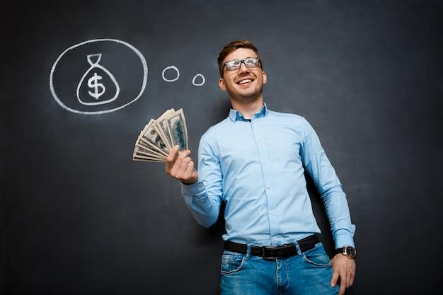 Retrato de homem ocupado segurando dólares nas mãos sobre o quadro-negro