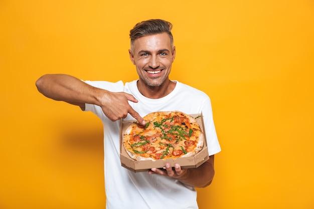 Retrato de homem otimista de 30 anos em uma camiseta branca segurando e comendo pizza em pé isolado no amarelo