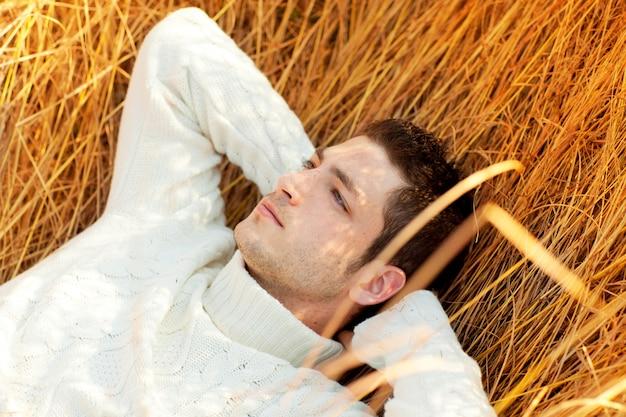 Retrato de homem outono inverno deitado na grama dourada