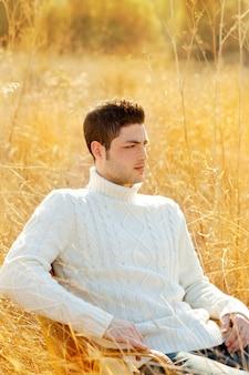 Retrato de homem outono inverno na relva seca ao ar livre