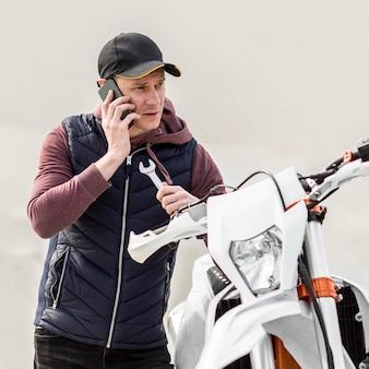 Retrato de homem pedindo ajuda para reparar moto