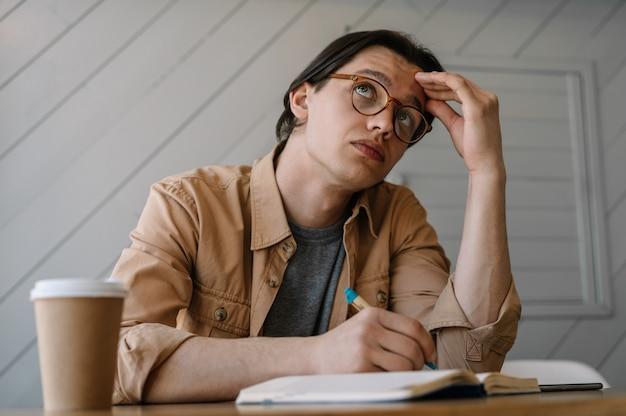 Retrato de homem pensativo em óculos elegantes, trabalhando em casa