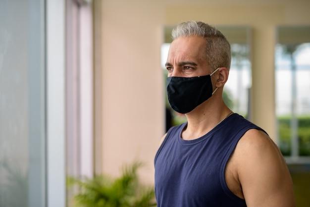 Retrato de homem persa maduro com máscara para proteção contra surto de vírus corona, distanciamento social na academia