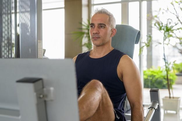 Retrato de homem persa maduro e bonito com cabelos grisalhos, fazendo exercícios na academia
