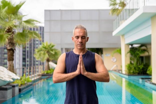 Retrato de homem persa maduro e bonito com cabelos grisalhos relaxando na piscina no telhado