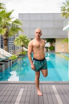 Retrato de homem persa maduro e bonito com cabelos grisalhos sem camisa na piscina no terraço