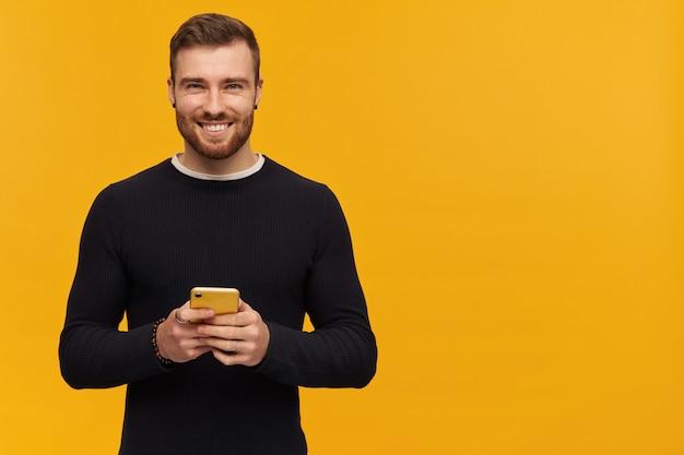 Retrato de homem positivo com cabelo castanho e cerdas. tem piercing. vestindo um suéter preto. segurando o telefone celular. . copie o espaço à direita, isolado sobre a parede amarela