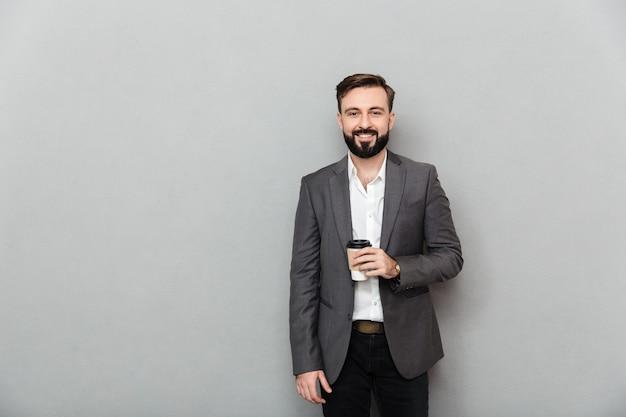 Retrato de homem positivo na camisa branca, posando na câmera com um amplo sorriso e segurando café para viagem sobre cinza