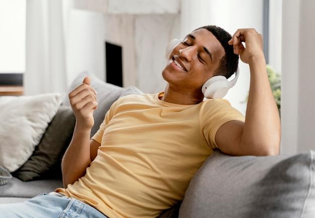 Retrato de homem relaxando em casa enquanto ouve música