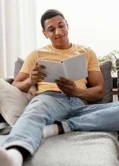 Retrato de homem relaxando em casa lendo
