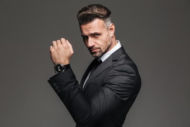 Retrato de homem rico bonito 30 anos de terno preto, posando com elegante relógio no pulso, isolado sobre grafite