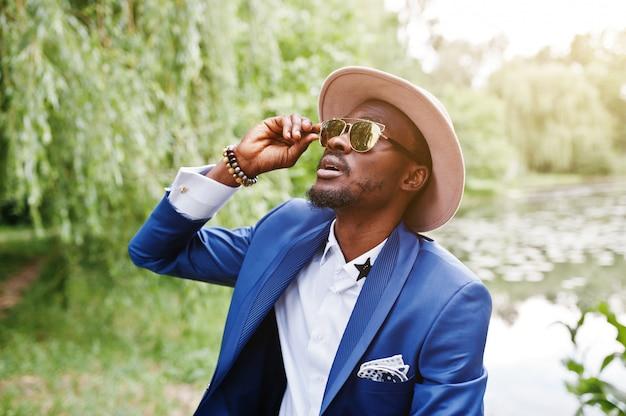 Retrato de homem rico e elegante preto no casaco azul, chapéu e óculos de sol