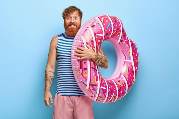 Retrato de homem ruivo sorridente e despreocupado posando com piscina de donuts flutuante