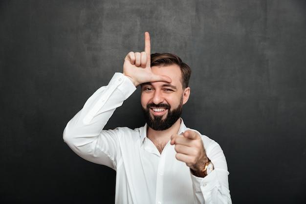Retrato de homem sarcástico, mostrando sinal de perdedor na testa e apontando na câmera com sorriso, zombando ou humilhar sobre parede de grafite