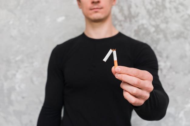 Retrato, de, homem, segurando, cigarro quebrado
