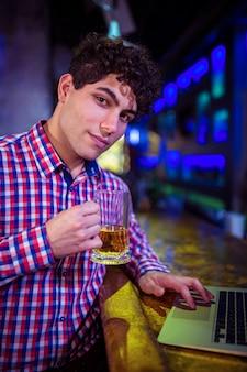 Retrato de homem segurando copo de cerveja no balcão de bar