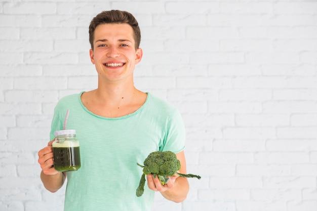 Retrato, de, homem, segurando, fresco, brócolos, smoothie, jarro