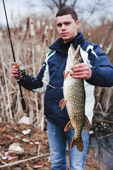 Retrato, de, homem, segurando, grande, pegado, peixe, e, cana de pesca