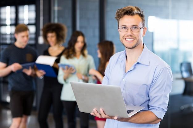 Retrato, de, homem, segurando, um, laptop, e, sorrindo, enquanto, colegas, estar, em, escritório