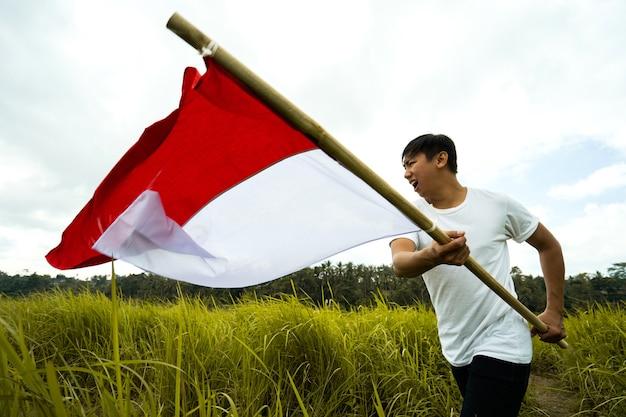 Retrato de homem segurando uma bandeira da indonésia
