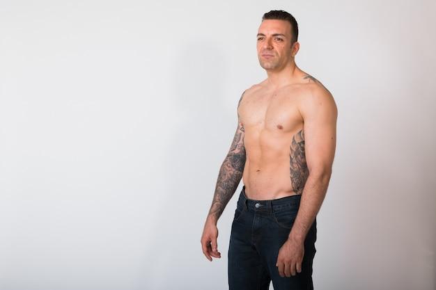 Retrato de homem sem camisa com tatuagens na parede branca