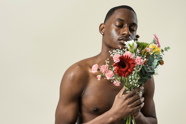 Retrato de homem sem camisa posando com buquê de flores e espaço de cópia