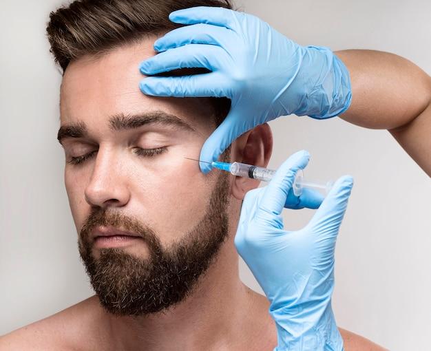 Retrato de homem sendo injetado em seu rosto