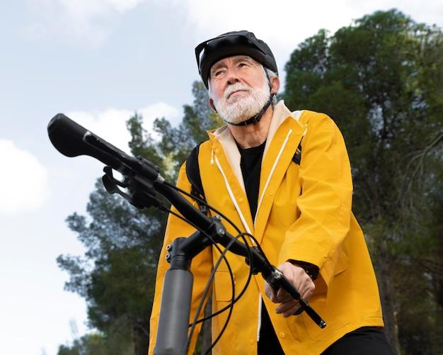 Retrato de homem sênior com bicicleta na montanha Foto Premium