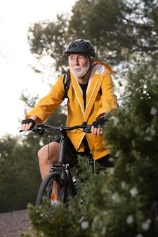 Retrato de homem sênior com bicicleta na montanha