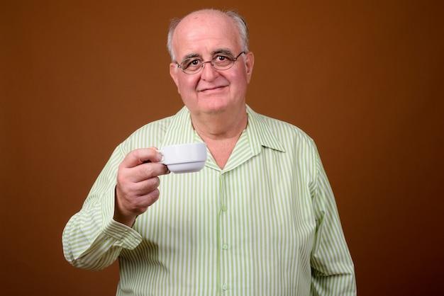 Retrato de homem sênior com excesso de peso segurando uma xícara de café