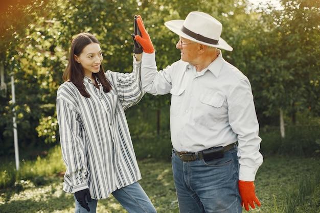 Retrato de homem sênior com um chapéu de jardinagem com a neta