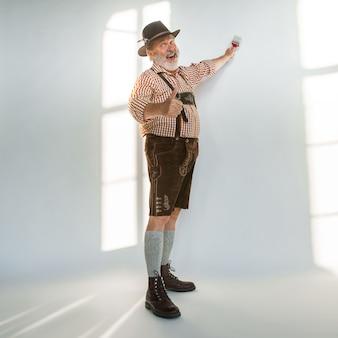 Retrato de homem sênior da oktoberfest com chapéu, vestindo as roupas tradicionais da baviera. tiro completo masculino no estúdio em fundo branco. a celebração, feriados, conceito de festival. pintando uma parede.