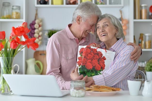 Retrato de homem sênior dando um presente para uma mulher
