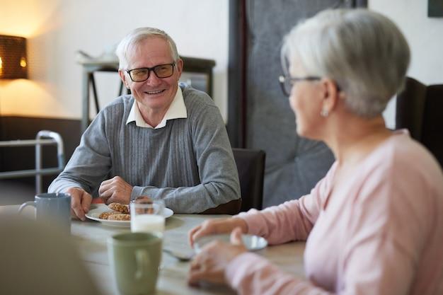 Retrato de homem sênior de cabelos brancos, sorrindo alegremente enquanto toma o café da manhã na sala de jantar do berçário.